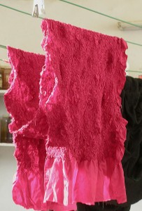 After the dyeing, the scarf is left to dry before removing ties.