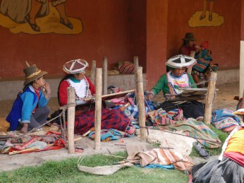 Group of Pitumarca weavers talking and weaving.