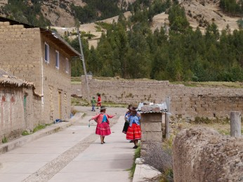 Women walking and spinning in the streets of Pitumarca.