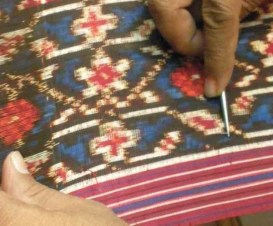 A fine pick is used to perfect the alignment of weft and warp threads in the fabric. Note the feathering of the edges of the designs.