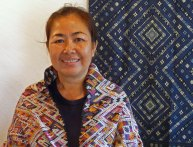 Ms. Sisane surrounded by exquisite Lao traditional supplementary weft silk weavings.