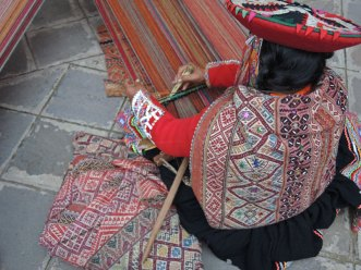 A woman from Accha Alta demonstrates her weaving technique during Tinkuy. (Note the narrow white beads and colorful sequins on the back of her manta.)