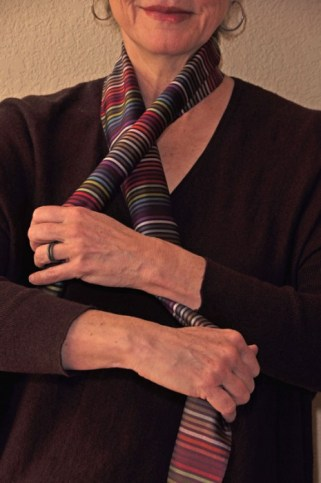 Hold the short end of the scarf in your left hand. The longer end of the scarf is in your right hand, the end of the scarf trailing down. Cross your left hand over the right-hand scarf just above the hold.