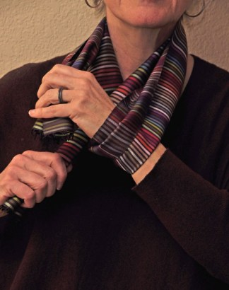 Now reverse hands: Release the scarf end in your left hand, and grab the end from your right. Your right hand grabs hold of the end from your left hand.