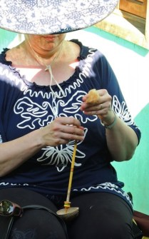 Anita Osterhaug spinning brown cotton using a traditional handspindle and carved support gourd bowl.