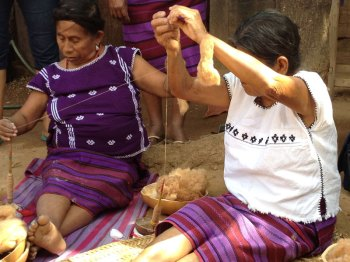 Women spinning brown cotton on traditional support spindles in Oaxaca.
