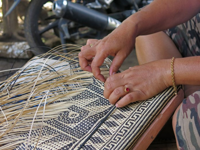 The intricate pattern is handwoven using naturally dyed black and natural rattan. The artisan is from the Eheng village.