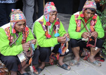 The men from Sallac knitting traditional hats. Note that they are also wearing knitted vests.
