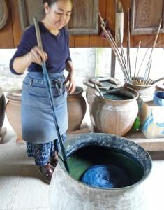 Bouasonkham Sisane, of the Lao-Japan Traditional Culture Center in Vientiane, Laos, stirs the indigo dye pot.