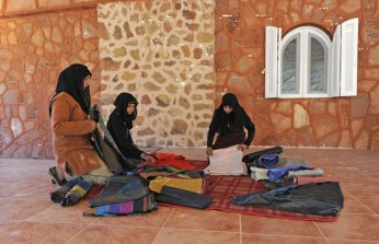 Preparing fabric kits to be embroidered by the women artisans