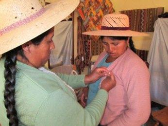 Doña Beatris receives her Spinzilla pin from Doña Maxima.