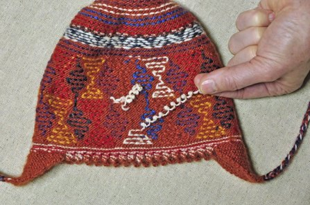 The inside of a hat showing a string of q'urpu.