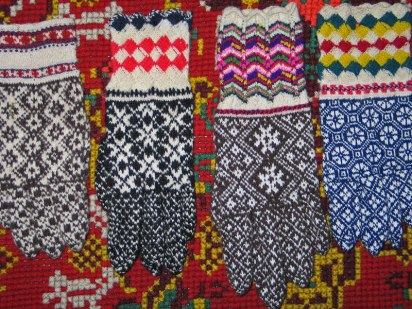 A collection of Kihnu gloves with different cuffs and hand motifs.