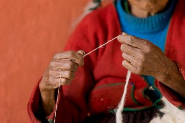 Emilia's skillful hands can spin yarn of even tension just by feel.