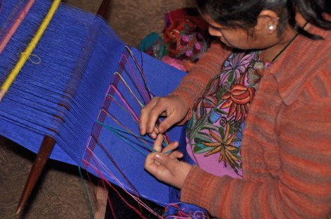 Brocade weaving on a backstrap loom continues. Note her embroidered blouse.