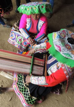 Women weave very finely detailed scarves and wrapping cloths on backstrap looms.