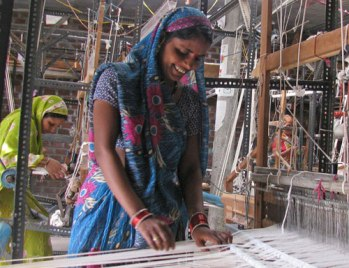 Women prepping weaving on floor looms in India