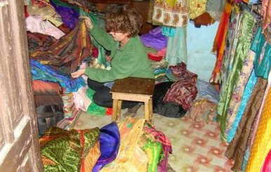 Julie digs through piles of damaged sarees selecting colorways for the scarves.