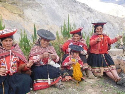 Women from Accha Alta spinning while a child winds a ball of yarn. Photo credit: Barry Chant