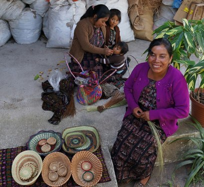 Josefina (forefront) works on base of a new basket using a coiling technique.