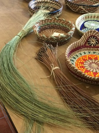 Basket making materials include wild grass (left) and pine needles, as well as raffia for stitching.