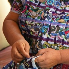 Lola Sapalú embroiders a new huipil, covering it with fanciful birds.
