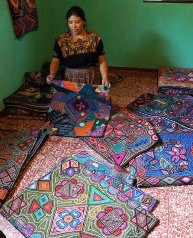 Glendy shows off the many hooked rugs made by her and other artisans.