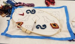 A sample of implements used to hook rugs: monk's cloth, a hoop to hold the fabric taut, stripped rags, and the hook for pulling fabric through the cloth.