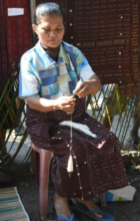 One of many ways of spinning cotton in Bama village, east Flores. Note the carded punis in her lap of her exquisite handwoven sarong.