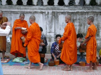 Early morning alms. The monks gather their rice for the day.