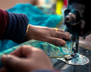 The sewing of the two layers of hand-stitched kantha cloth is done by machine.