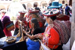 The artisans from the Peruvian highlands watch Navajo weaver Barbara Ornelas.