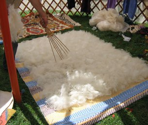 Fluffing fiber with a wooden rake, similar to the bowing process.