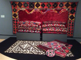 Entrance to exhibit: The backdrop is a tush ki'iz, a large-scale patchwork panel hung in a Kyrgyz yurt (boz üy) along with bedding and pillows. A Shyrdak felt carpet is in foreground.