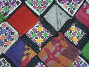Back side of patchwork quilt showing detail of embroidery along with ikat fabric patches sewn together; my collection.