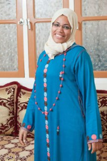 Rachida wears a traditional djellaba with hand-embroidered trim and a button necklace to match. Photo credit: Joe Coca