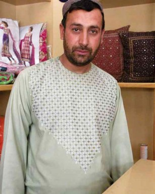 The manager of one of the Kandahar Treasure shops wears a splendid example of traditional khamak. Photo credit: Mary Littrell