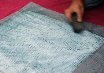 The pattern is brushed through the stencil; the stencil is on top of the fabric.