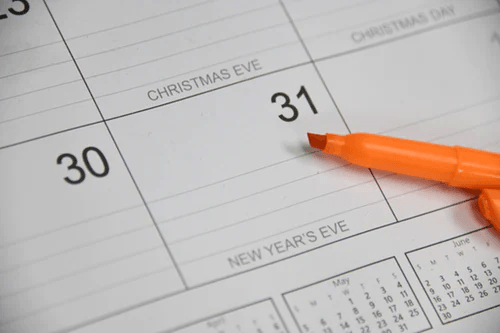 A white calendar and an orange highlighter.
