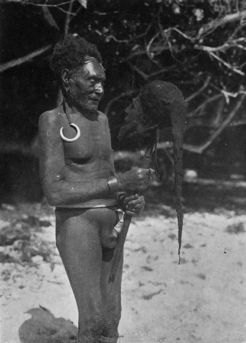 An image from the 1934 book <em>Malekula: A Vanishing People in the New Hebrides</em>, showing a man holding a cured head wearing a spider web cap.