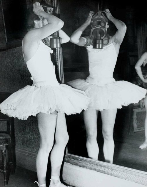 A ballerina tries on a gas mask, Paris, 1939.
