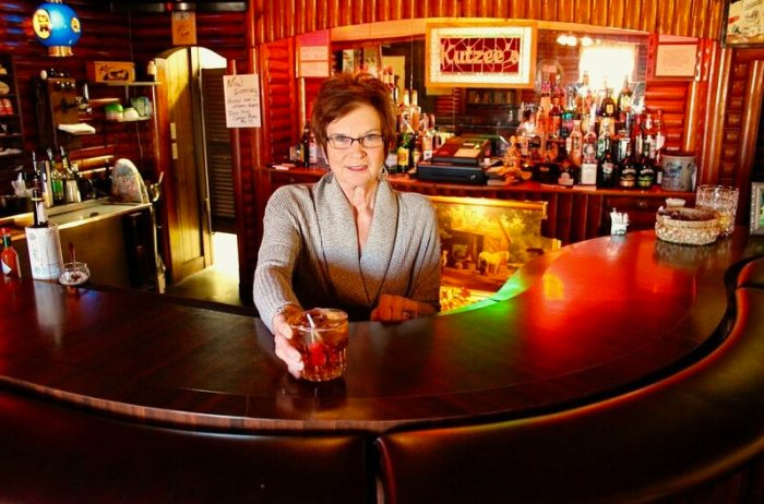 """Kutzee's Supper Club, with Kathy """"Kutzee"""" Babich behind the bar with a brandy Old Fashioned."""
