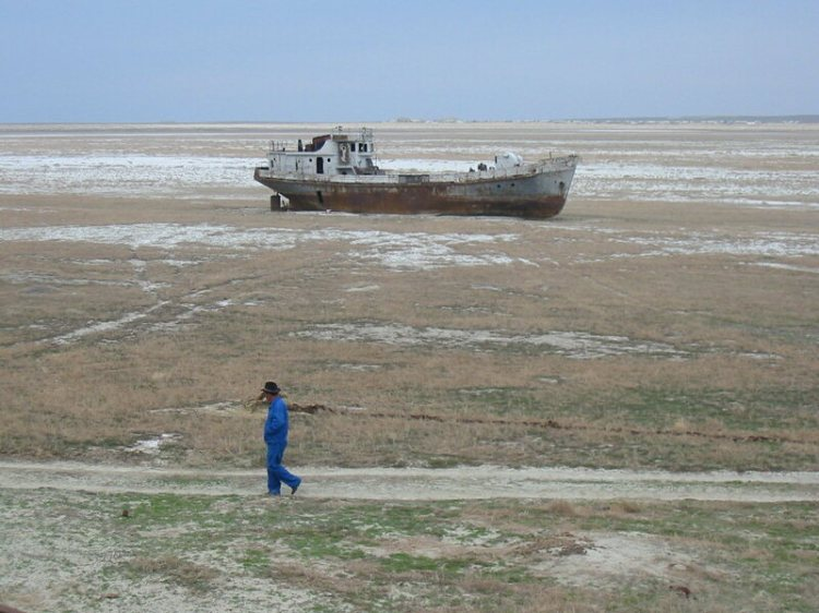 A man walks past an orphaned ship rusting away in the desert.