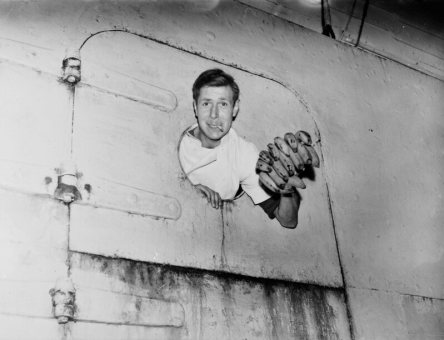 A sailor leans out of a porthole on the SS <em>Tilapa</em>, the first ship to bring bananas into Britain after the Second World War, at Avonmouth Dock, Bristol.