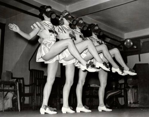 London chorus girls rehearse in their gas masks, 1939.