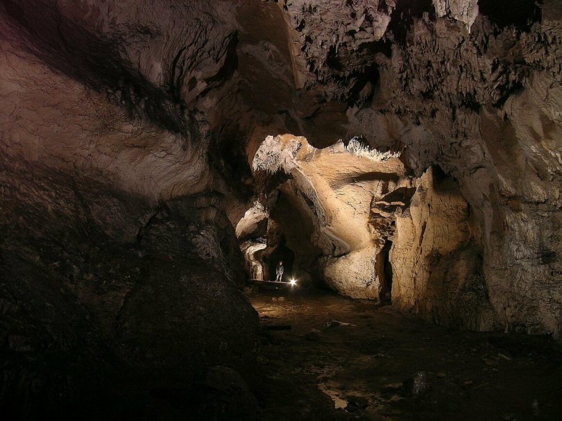 The lower gallery of Atxurra Cave illuminated by harsh, static modern lighting.