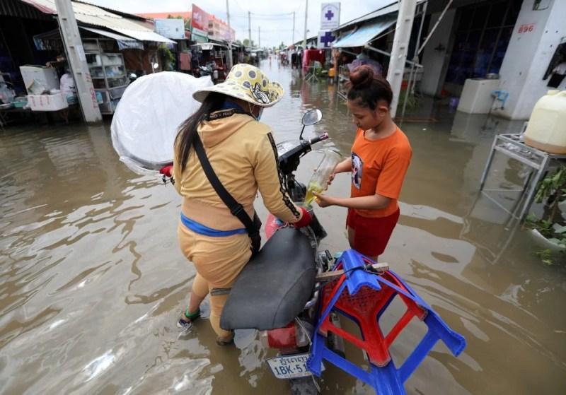 Seorang penduduk mengisi petrol untuk motosikalnya di sebuah kampung yang terjejas akibat banjir di Phnom Penh, Kemboja. - Foto EPA
