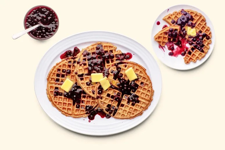 A platter of whole wheat oat waffles with butter and berries