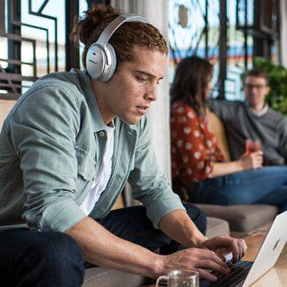 Persona escuchando música con los audífonos QuietComfort 35
