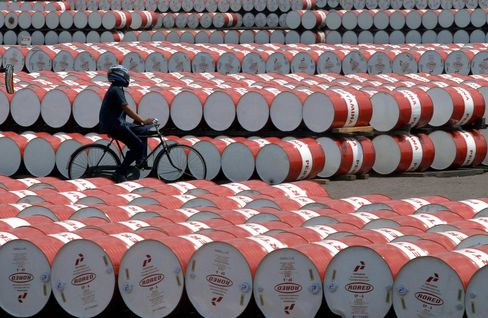 A worker cycles past oil barrels in Jakarta.